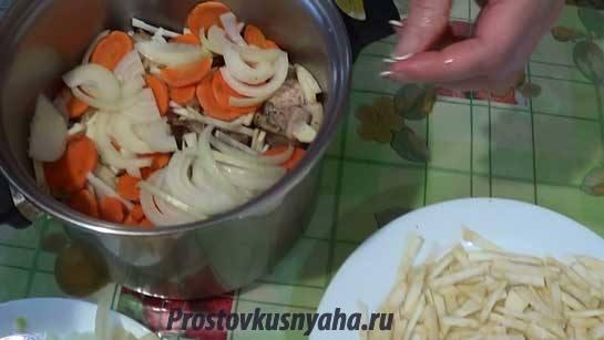 Выкладываем шарами сельдерей, морковь, лук, сверху — кусочки кролика